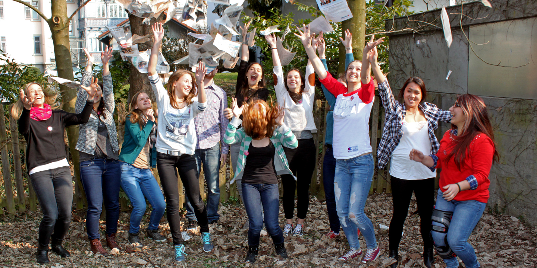 Eine Gruppe von Jugendlichen springt in die Höhe und wirft dabei Zeitungsaritkel fröhlich in die Luft.