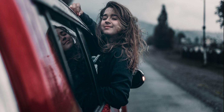Jugendliche die ein Selfie von sich als Beifahrerin macht und lacht.