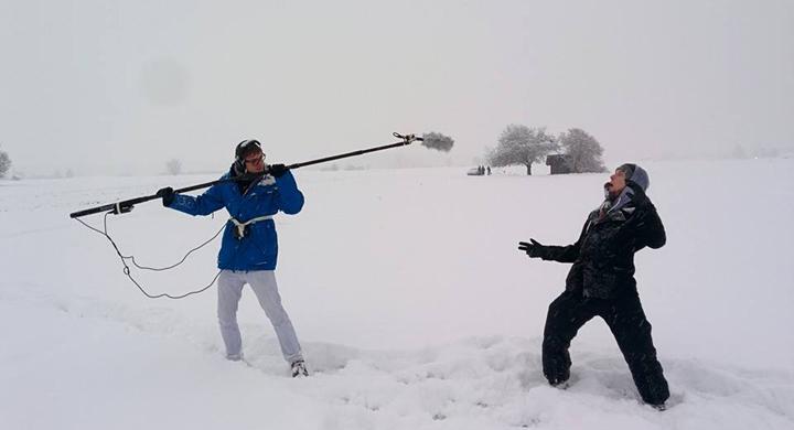 Jugendliche im Schnee mit Stabmikrofon