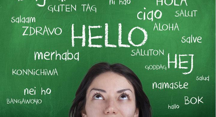 Jugendliche vor einer Tafel mit dem Wort hallo in verschiednene Sprachen