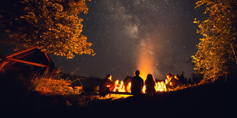zwei Jugendliche sitzen vor einem Lagerfeuer unterm Sternenhimmel