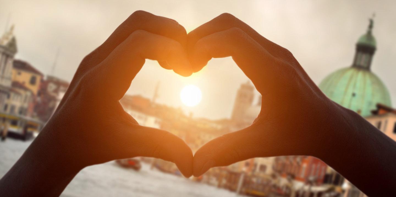 Herz geformt durch Hände im Hintergrund Sonnenuntergang