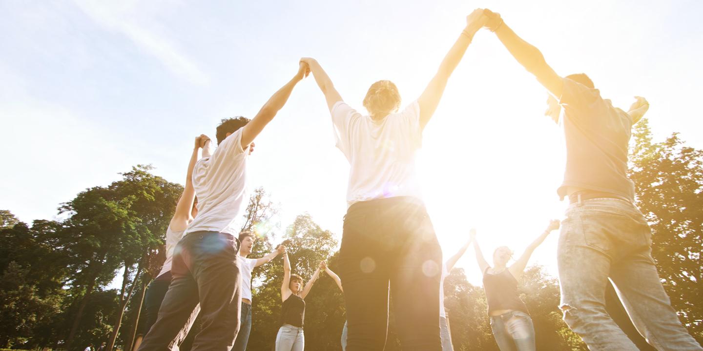 Jugendliche halten sich an ihren hochgestreckten Händen.