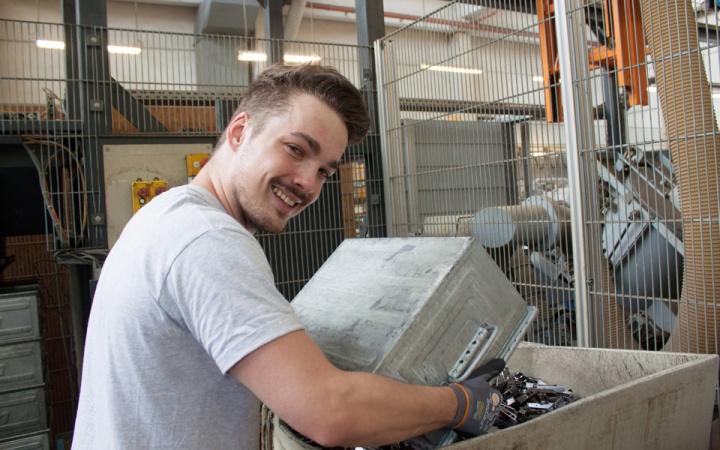 Jugendlicher leert eine Kiste voller Metal aus