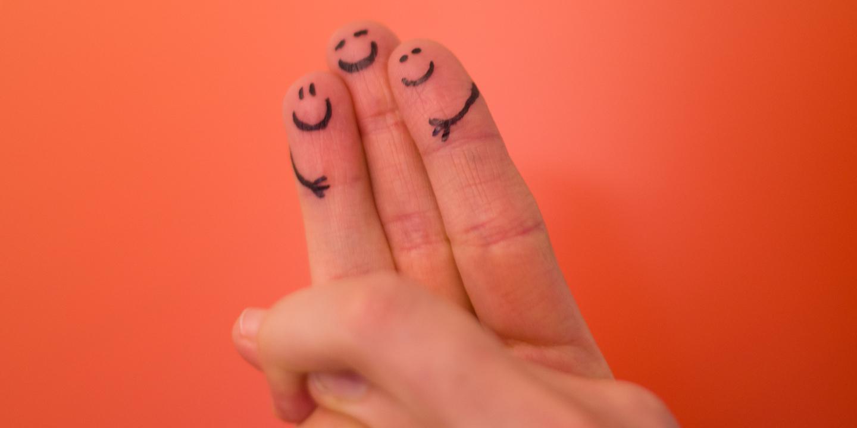 Drei Finger mit aufgemalten Gesichtern halten sich.