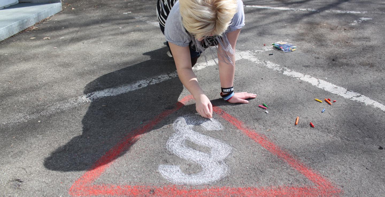 Jugendlichen zeichnet ein Paragraphensymbol auf den Boden