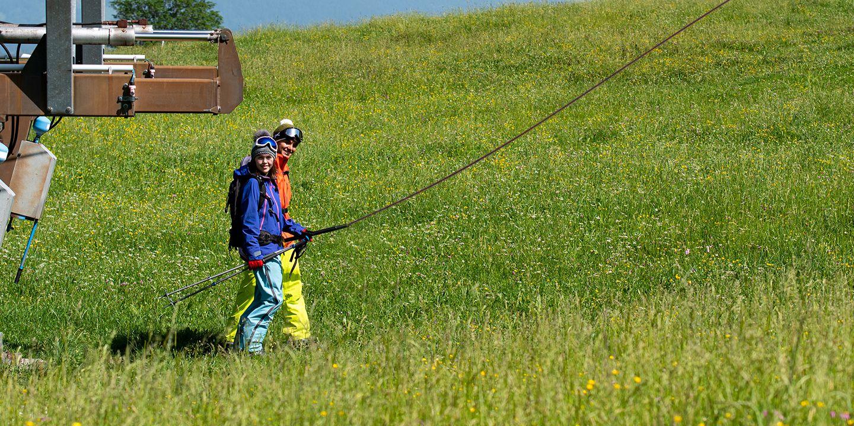 zwei Jugendliche stehen in einer Wiese mit voller Skiausrüstung und SChlepplift.