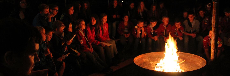 Pfadfinderinnen und Pfadfinder sitzen rund um ein Feuer.