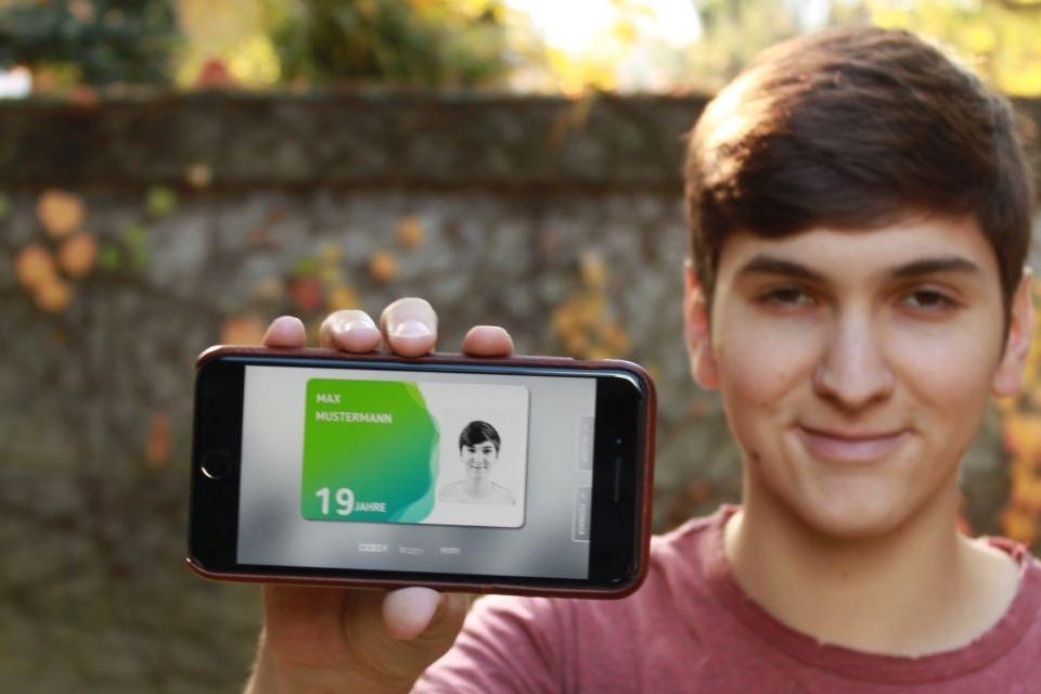 Jugendlicher zeigt auf seinem Handy die aha card im App