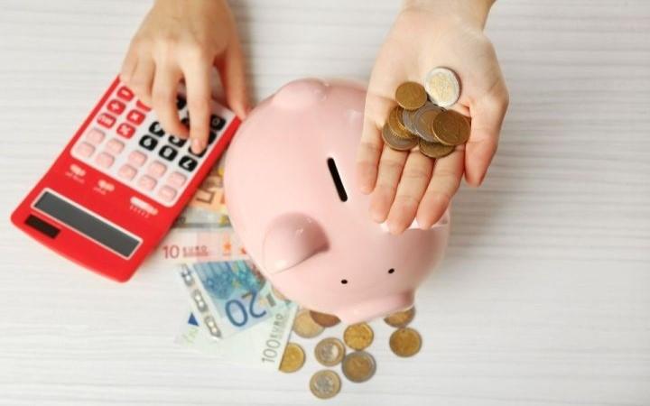 Eine Hand hält Münzen, eine Hand tippt am Taschenrechner, Sparschwein
