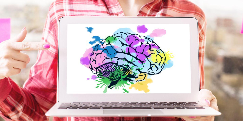 Person mit Laptop in der Hand auf dem man ein buntes Gehirn sieht.