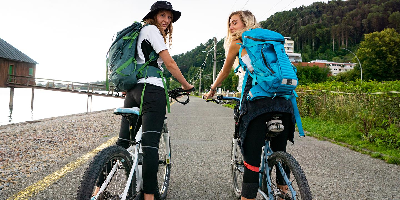 Zwei Jugendliche mit Rücksäcken auf dem Fahrrad am Bodenseeradweg in Bregenz.