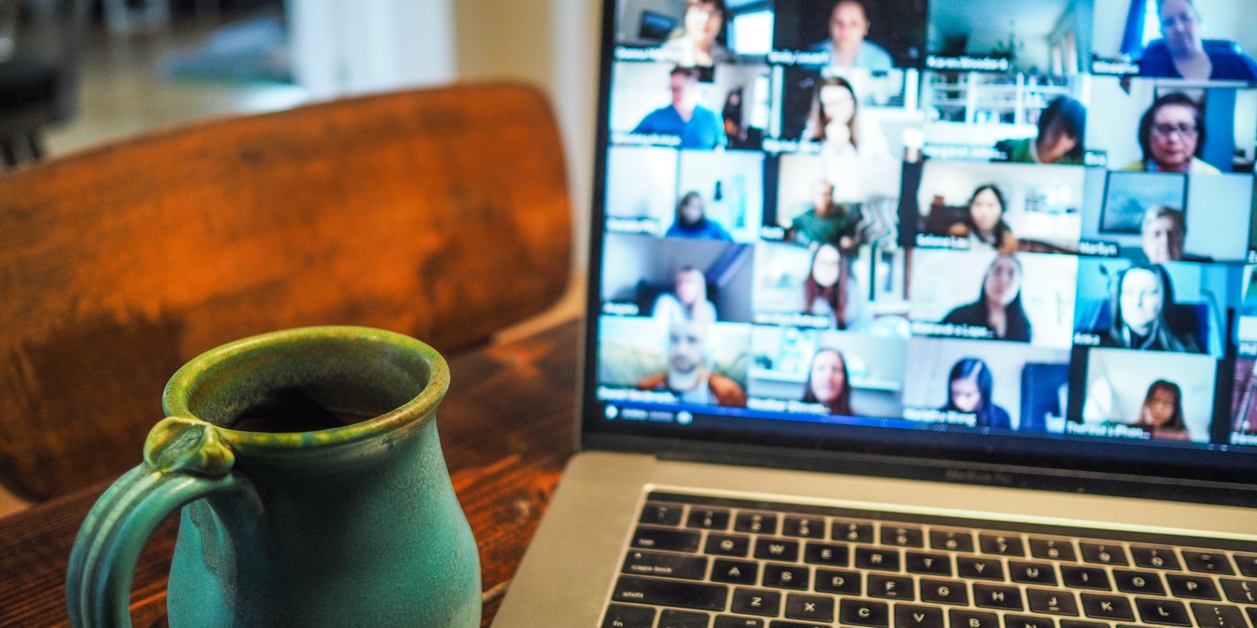 Tasse vor einem Laptop mit einem Online-Meeting am Screen