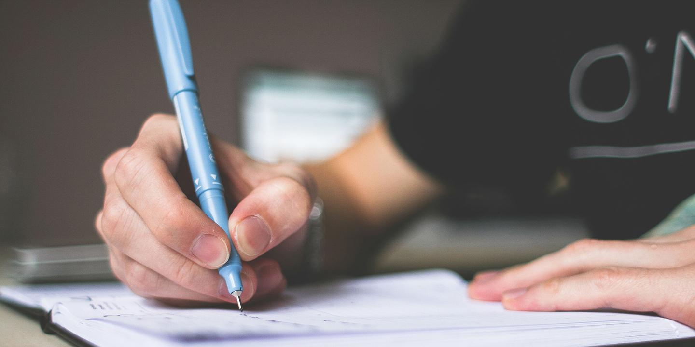 Jemand schreibt mit einem hellblauen Stifft in ein Heft.