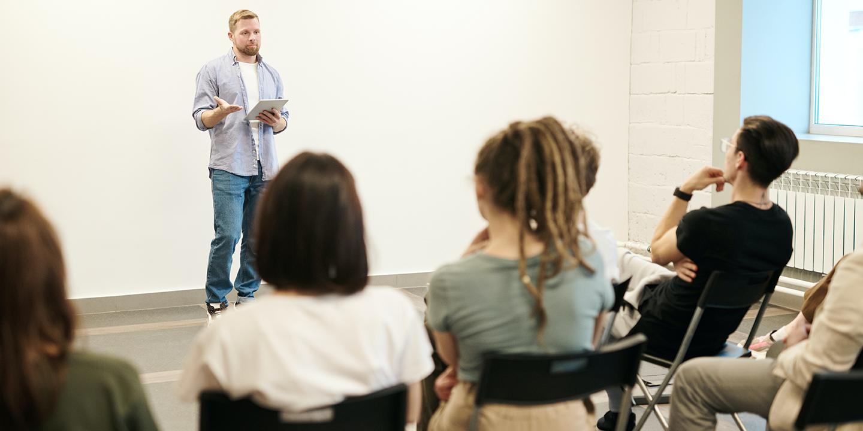 Ein Mann hält einen Vortrag vor einer Gruppe.